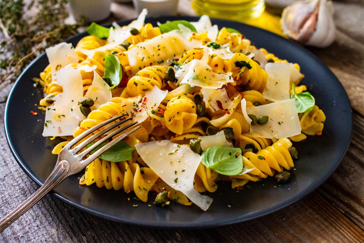 Pasta With Parmesan And Caper On Wooden Table